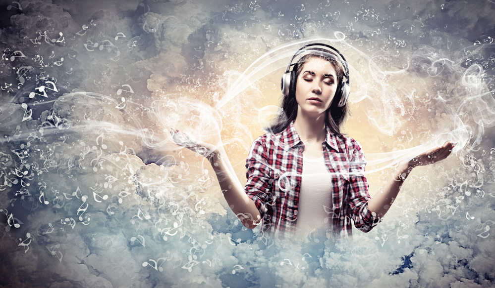 Image of young pretty woman with headphones meditating