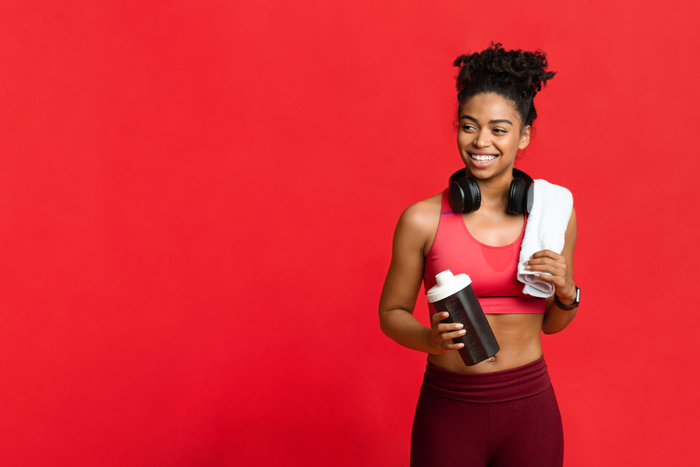 Happy african fitness girl with towel on her shoulder and wireless headset holding bottle with protein, looking at copy space
